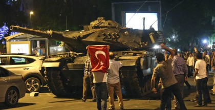 """A tank moves into position as Turkish people attempt to stop them, in Ankara, Turkey, early Saturday, July 16, 2016. Turkey's armed forces said it """"fully seized control"""" of the country Friday and its president responded by calling on Turks to take to the streets in a show of support for the government. A loud explosion was heard in the capital, Ankara, fighter jets buzzed overhead, gunfire erupted outside military headquarters and vehicles blocked two major bridges in Istanbul. (AP Photo)"""